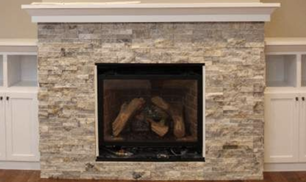 Rectangle shaped stone veneers in a white to off brown tone surrounding a black fireplace with a white mantle