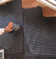 A staple gun being used to secure lath in preparation for a scratch coat application