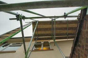 A photo taken from underneath a section of scaffolding being used to apply stucco to a house