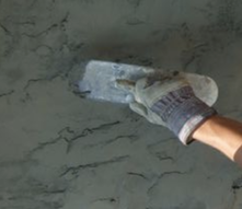 Stucco application process displaying a gloved hand using a trowel to apply cement